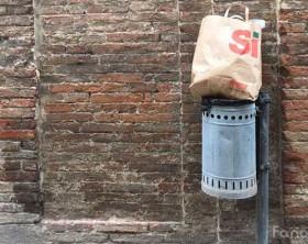 Un bidone riempito di spazzatura davanti a un ufficio comunale